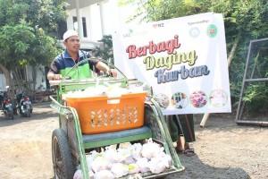Salah satu pengurus Laz Sidogiri mendistribusikan daging kurban ke rumah penduduk