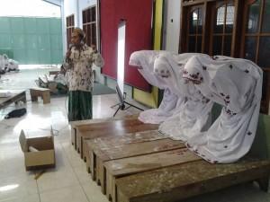 Santriwati mempraktekkan cara rukuk versi wanita yang benar, dipandu oleh Ust. Ali Ghafir, relawan LAZ Sidogiri