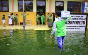 Relawan LAZ Sidogiri menuju perataran SDN SDN Kadungringin IV yang dingenangi air setingti lutut orang dewasa